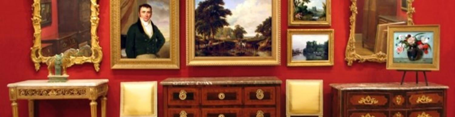 Red wall with paintings and antique furniture